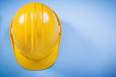 Yellow building helmet on blue surface construction concept