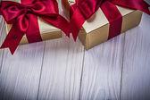 Zlaté dárkové krabičky s červené pásky na dřevěné desce svátky concep