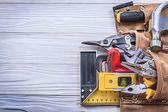 Fotografie Kožené toolbelt s stavební náčiní na dřevěné desce s kopií