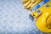 Fotografie Blue blueprints hard hat protective gloves construction level on