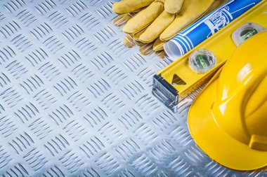 Blue blueprints hard hat protective gloves construction level on