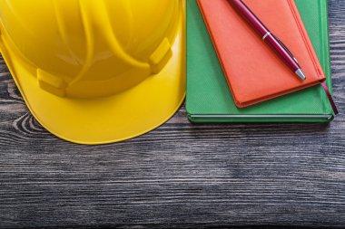 Notepads ball-point pen building helmet on wooden board construc