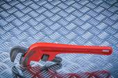 Fotografie Metal pipe wrench on corrugated metallic plate maintenance conce