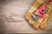 Photo Safety gloves pipe wrench on wooden board plumbing concept
