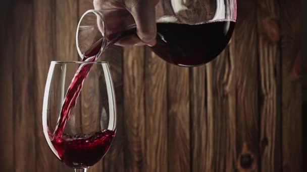 červené víno pomalu nalévání z karafy do sklenice na vinobraní dřeva pozadí