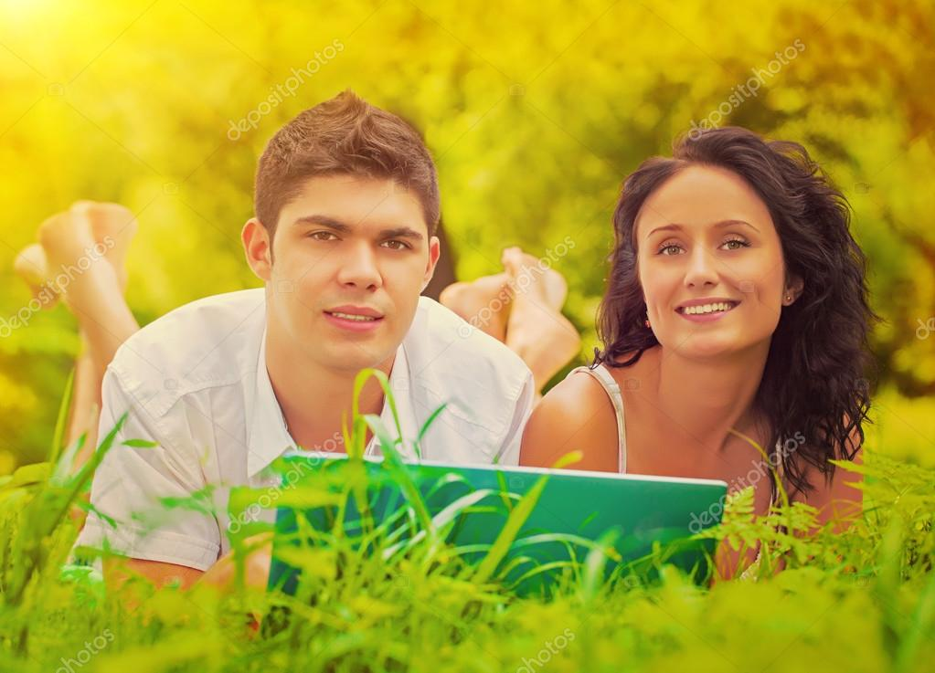 Young couple lying on grass smiling and looking at camera