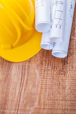 White blueprints and yellow helmet