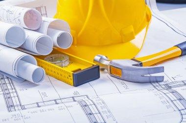 Construction tools, blueprints and helmet