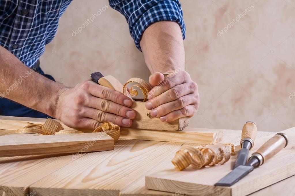 Hands of carpenter with woodworkers plane