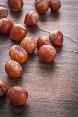 Several hazelnuts on wooden board