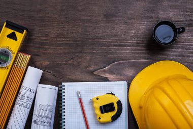 Workbook, pencil, coffee and construction objects