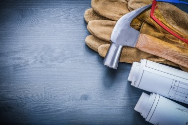 rolls of blueprints hammer gloves goggles