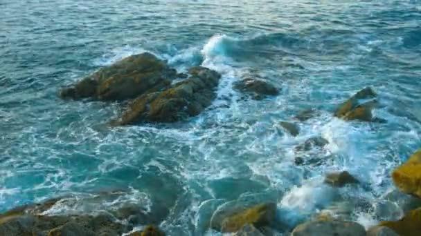 Večerní krajina. Skalnaté pobřeží oceánu. Vlny a velké kameny