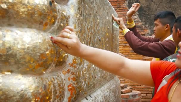 AYUTTHAYA. THAILAND - CIRCA FEB 2015: Worshippers Pressing coin on Gold Leaf onto Buddha Statue as an Offering at Wat Yai Chai Mongkhon.