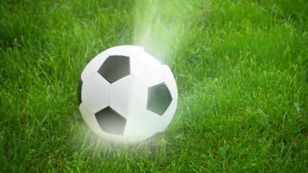 Fotbalový míč točí na poli s paprsky světla