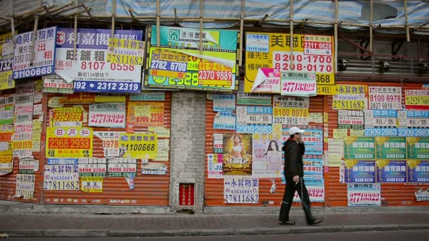HONG KONG. CHINA - CIRCA JAN 2015: Walls and roll up steel security doors at a local. public market. plastered over with commercial advertising signs.