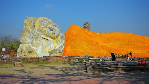 Lone buddhista imádat térdelt, és imádkozni, mielőtt egy hatalmas szobor a Buddha a Ayutthaya történeti Park Thaiföldön.