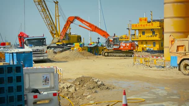Hydraulic excavator scoops up sand at a construction site on a beach in Hong Kong. China.