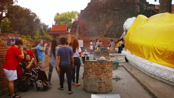 AYUTTHAYA. THAILAND - CIRCA FEB 2015: Buddhist Worshipers Line Up to Give Offerings to Buddha Sculpture at Wat Yai Chai Mongkhon.