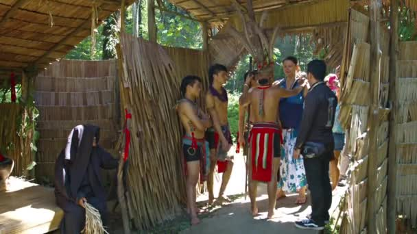 Local tribal chief in traditional clothes. greets tourists at the entrance to his hut at an educational cultural village on Borneo island