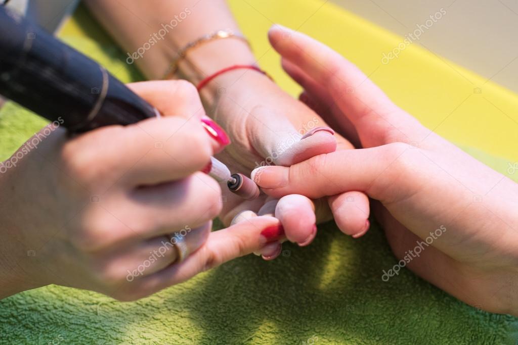 maestro utiliza una máquina eléctrica para quitar el esmalte de uñas ...