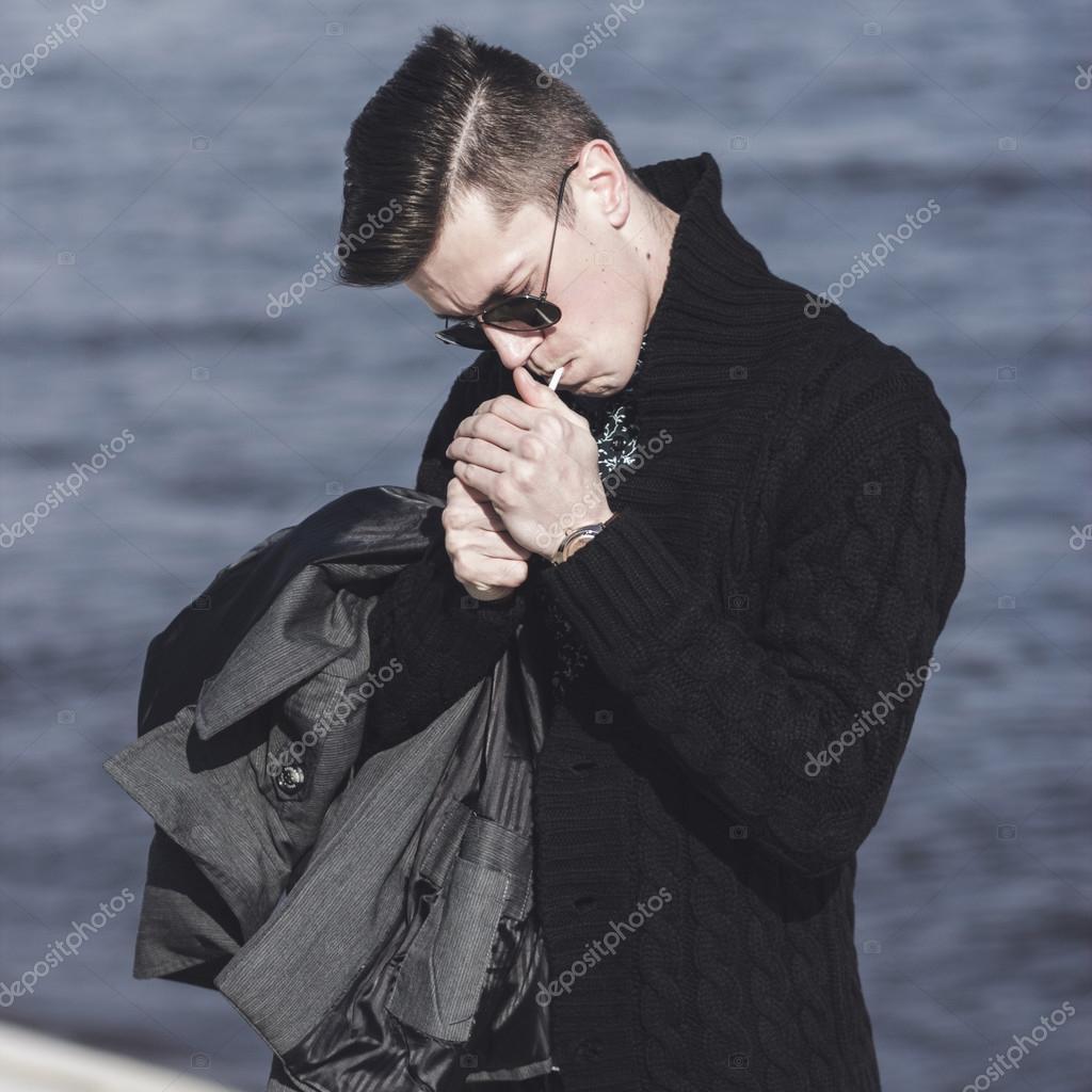 5a16f70778 Atractivo joven en gafas de sol de iluminación un cigarrillo — Foto de ...