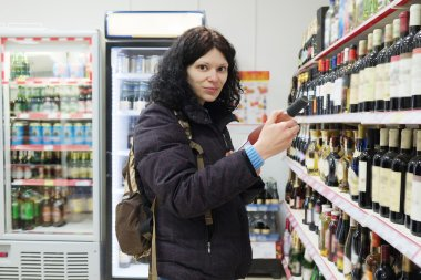 Woman choosing a the chips in supermarket
