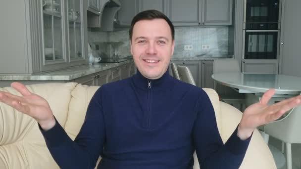 Junger erwachsener Mann breitet die Hände aus, grüßt und lacht, sitzt zu Hause auf der Couch und schaut in die Kamera, macht Live-Videokonferenz, Video-Chat-Konzept
