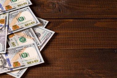 Heap of dollars bills on wooden surface