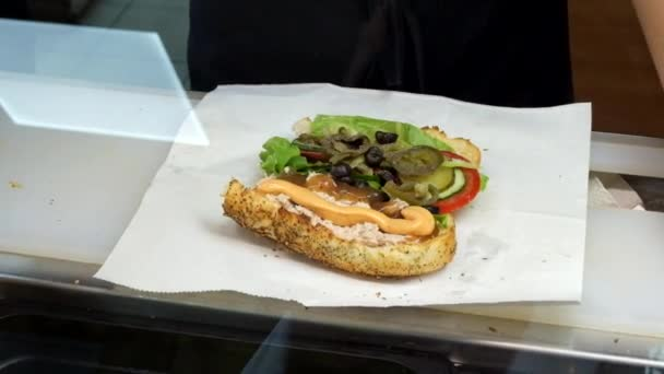 Delicious grilled cutlet sandwich plated with crunchy lettuce, tomatoes, and onions motion view.