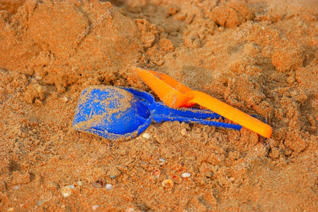 childrens sand toys , two shovels on snady surface