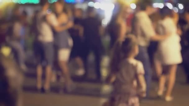 Many couples are dancing social dances in the street and there is little funny girl on foreground trying to compete