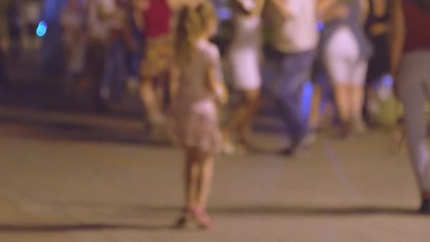 Crowd are dancing social dances in the street and there is little funny girl on foreground trying to imitate, defocused real-time shot.