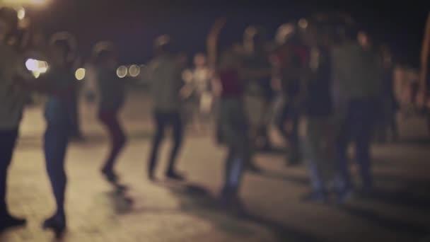 Viele Menschen tanzen in der Nacht auf der Straße. Salsa-Tanz unter freiem Himmel