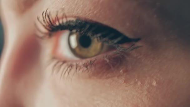 Velmi detailní záběr ženského oka s dlouhými řasami s řasenkou, třesoucí se ruční makro záběr