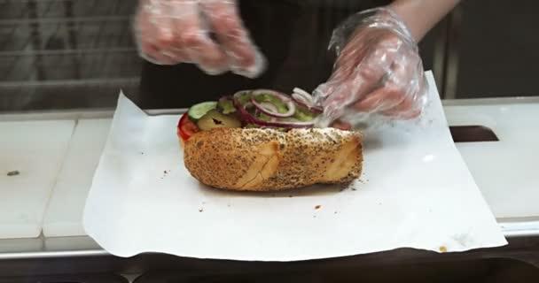 Nő átlátszó kesztyűben szendvicset készít papíron helyi gyorséttermi közelkép. Friss zöldség hozzáadása nyitott zsemlében.