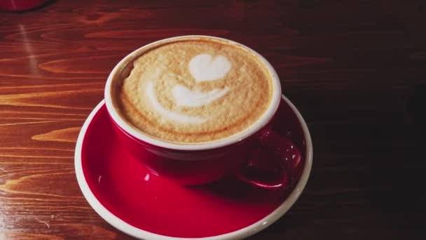 Dolly in shot of red cup of coffee on dark wooden table with froth art on top in heart shape