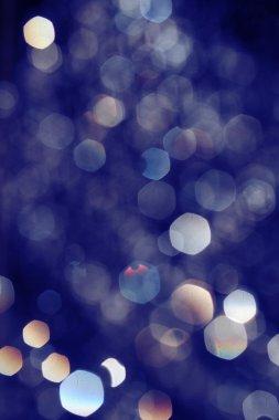 Toned in blue bokeh lights on black background, drops of water flying in the air defocused