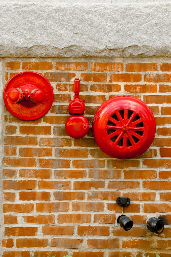 Red fire alarm sprinkler and hidrant in red brick wall