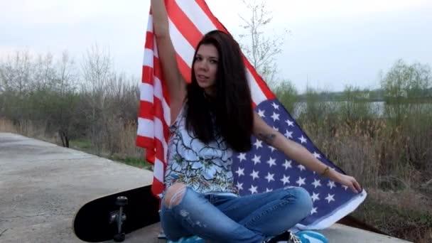 Felvétel a alkalmi divatos lány pózol gördeszka ül, és az amerikai zászló keresztezett lábak szabadban