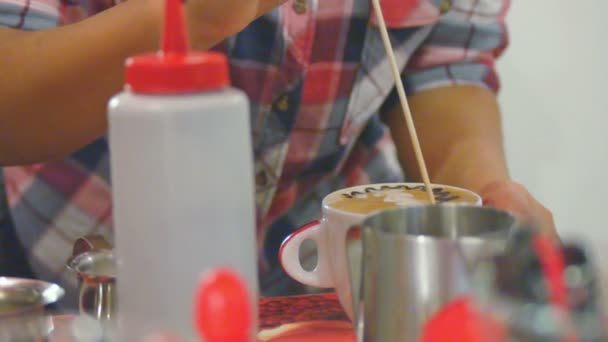 Barista is making latte art on milk foam