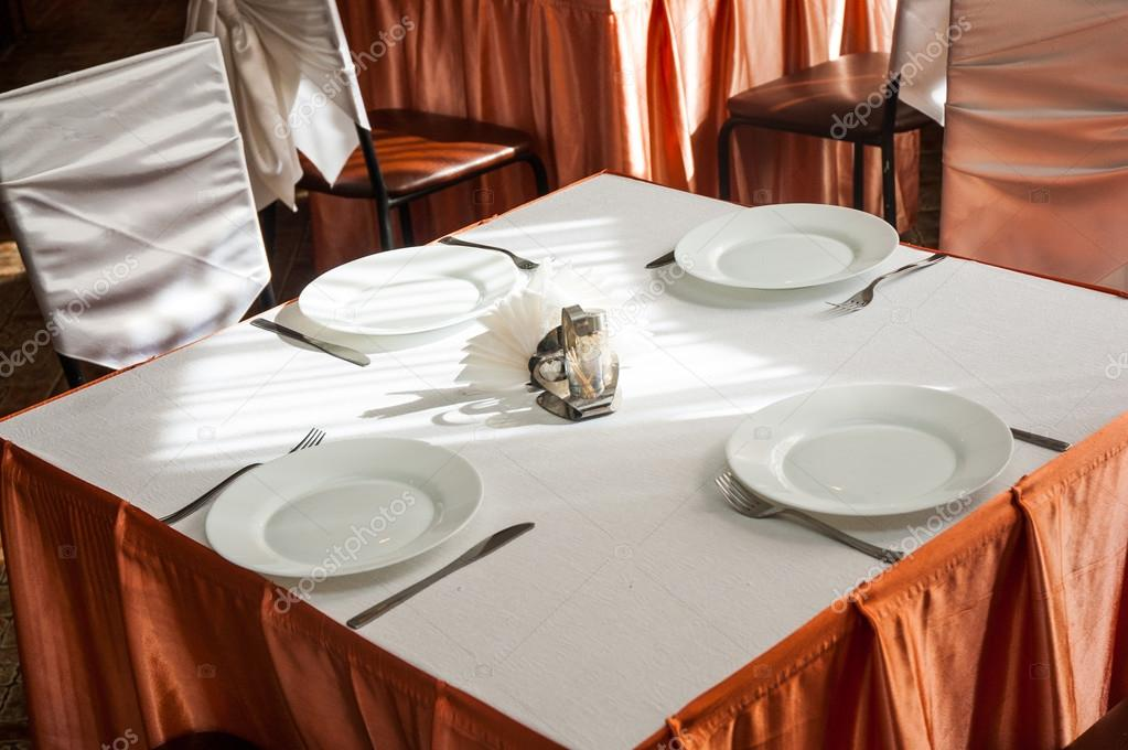 Empty white plate in a formal table setting on a table set with a white tablecloth & Empty white plate in a formal table setting on a table set with a ...