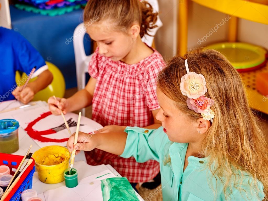 Gruppe kleine Mädchen mit dem Pinsel malen im kindergarten ...