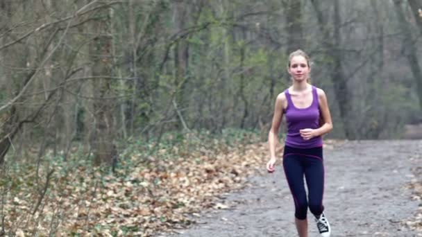 Woman runner is jogging on forest path in  park.