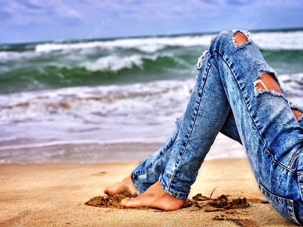 2666ac74 Nogi kobieta siedzi na wybrzeżu w pobliżu oceanu fal. Hot dog nogi ...
