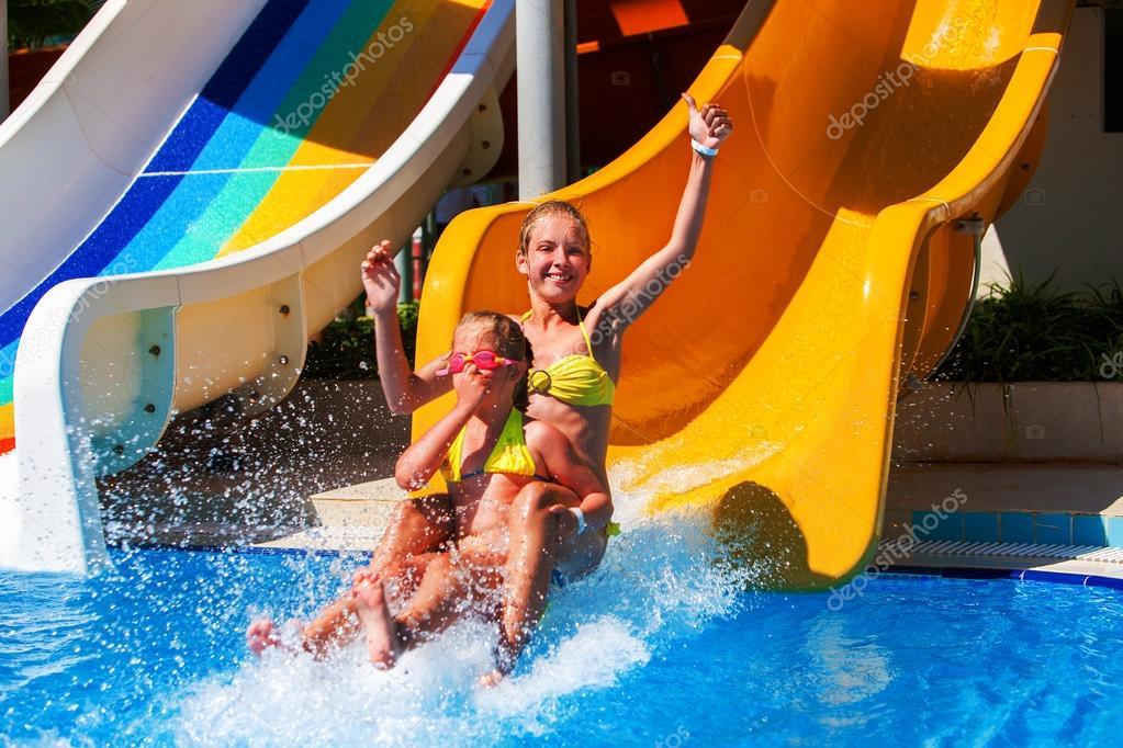 Kids on water slide at aquapark.
