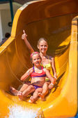 Kids turn out in air on water slide at aquapark.