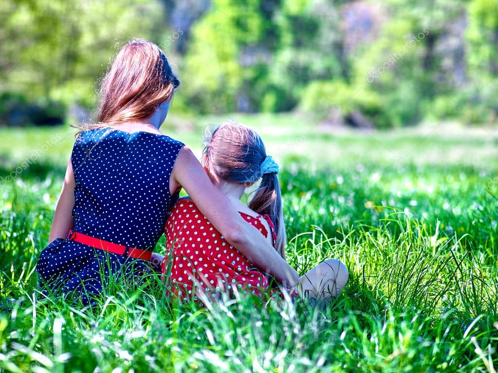 Girls wearing red and blue polka dots dress sitting on green grass into park.