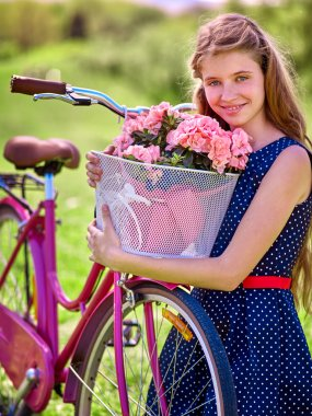Girl wearing blue polka dots sundress rides bicycle with flowers basket.