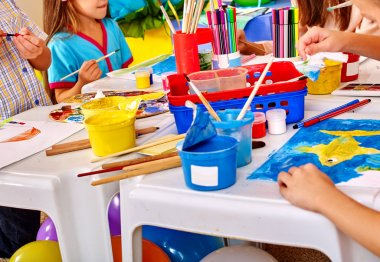 Children with teacher woman painting on paper in  kindergarten .